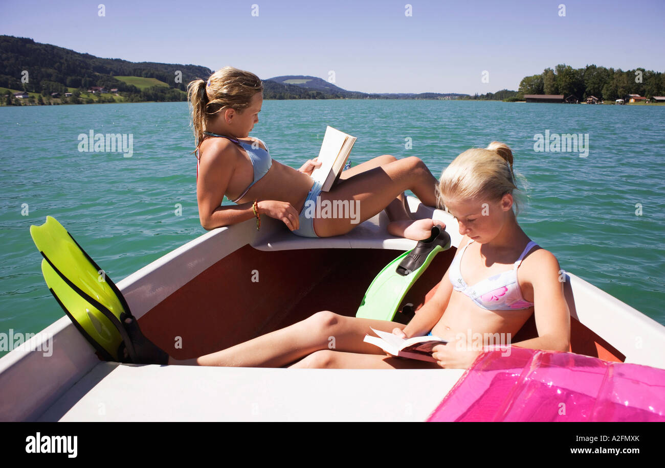Girls (13-15) sitting on boat, reading, side view - Stock Image