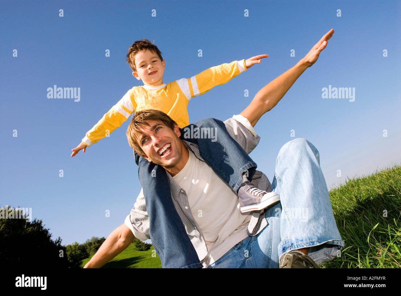 Boy (4-7) sitting on fathers shoulders, arms out - Stock Image
