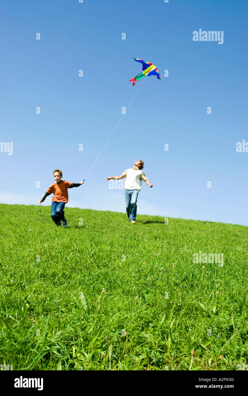Father and son (4-7) flying kite, low angle view - Stock Image