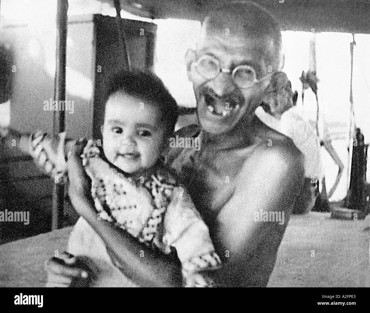 Mahatma Gandhi laughing playing with a child during his voyage on SS Rajputana to England September 1931 - Stock Image