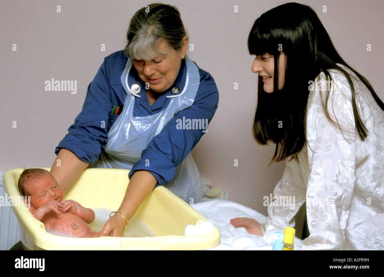 mature midwife helping new mother bathe her tiny newborn baby Stock ...