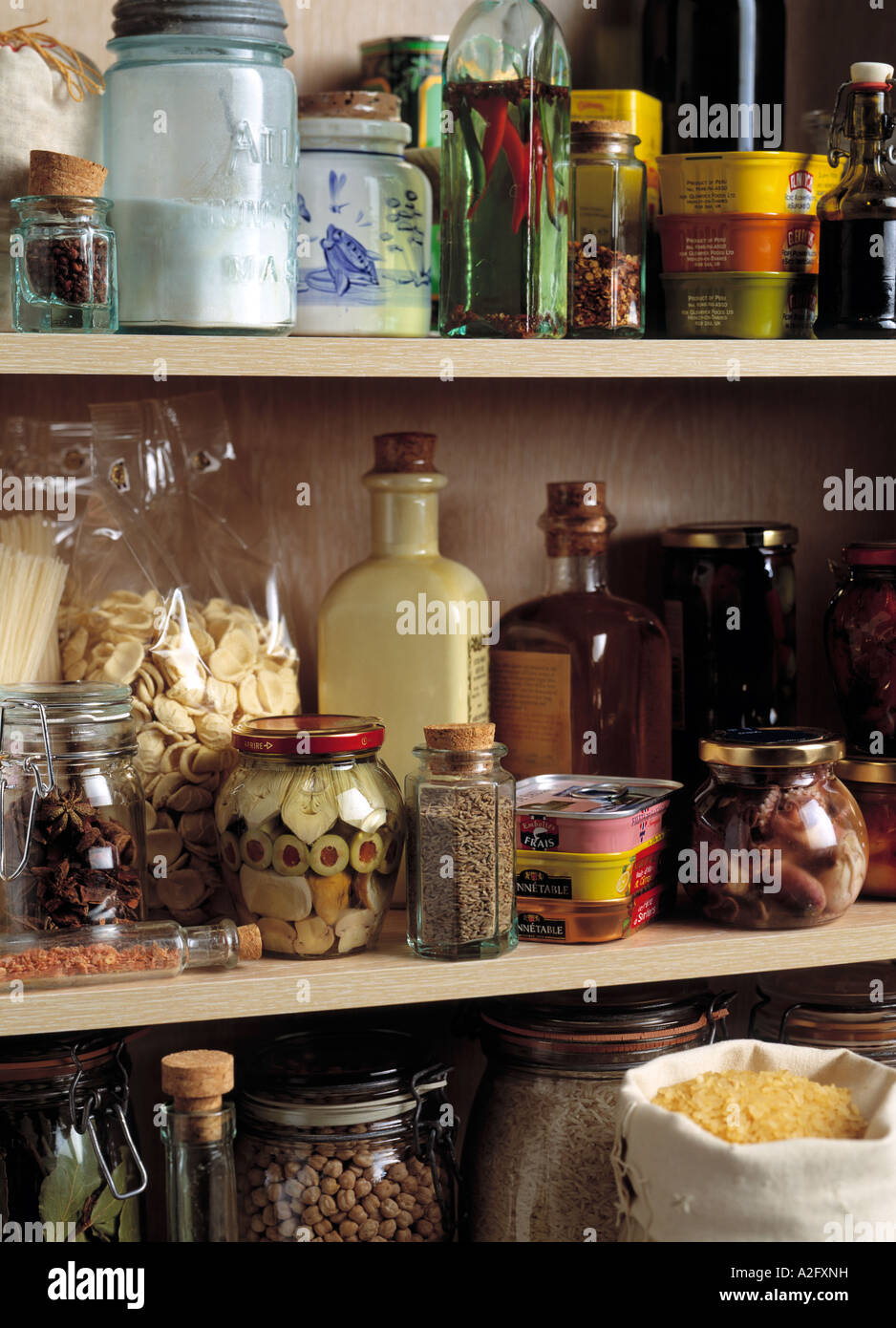 Shelves of a larder or store cupboard with dried and preserved food - Stock Image