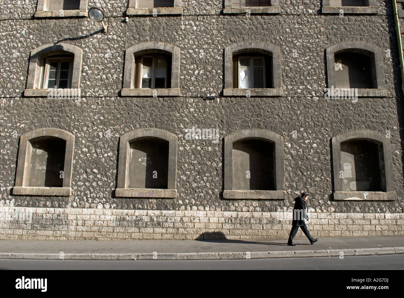 323 a young french male walks in front of the facade of an old warehouse - Stock Image