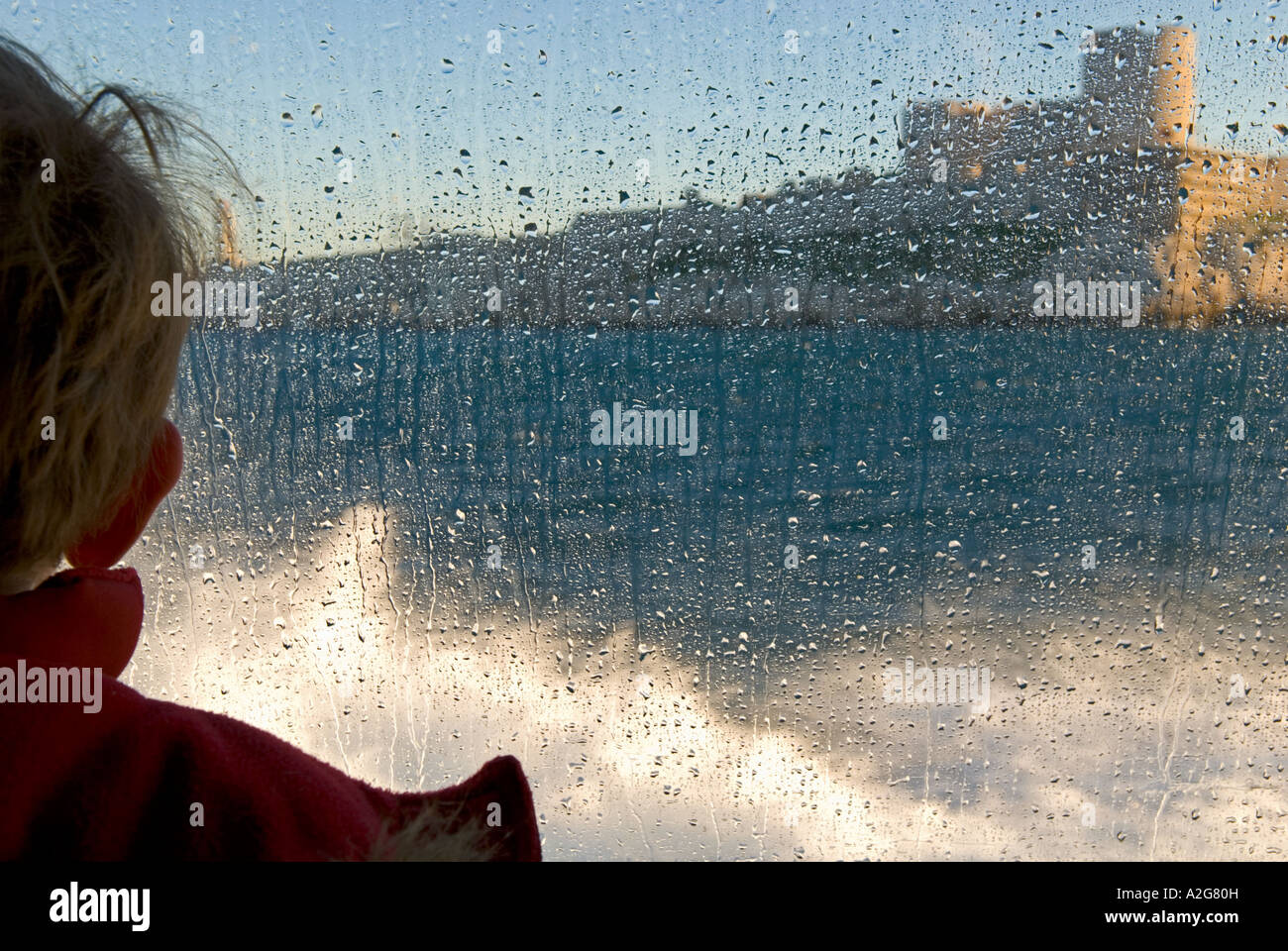 342 a cropped close up of a young boy on ferry looking through a window covered in water droplets - Stock Image