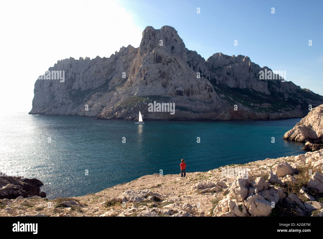 349 a little boy stands on a cliff overlooking a bay and island, watching a passing sailing boat - Stock Image
