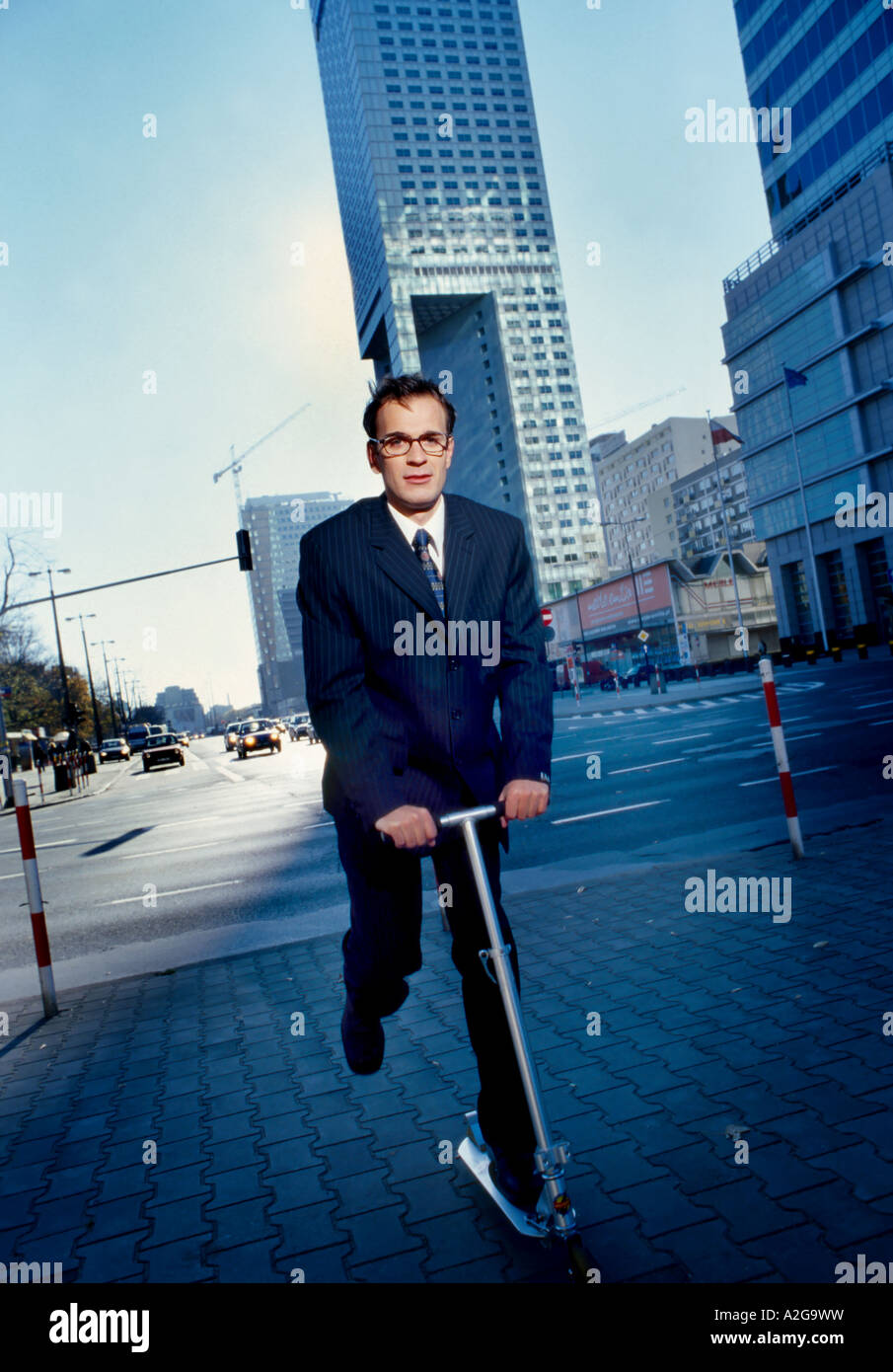 1213411 outdoor autumn day street building buildings street streets man young 25 30 dark haired glasses business - Stock Image
