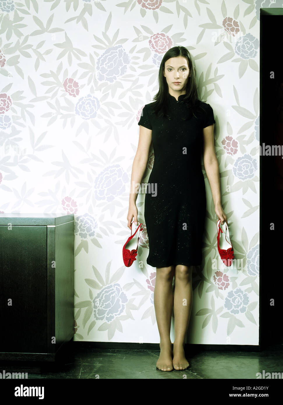 indoor flat room young woman 25 30 brunette long hair black dress red shoe shoes hold stand foot feet barefoot - Stock Image