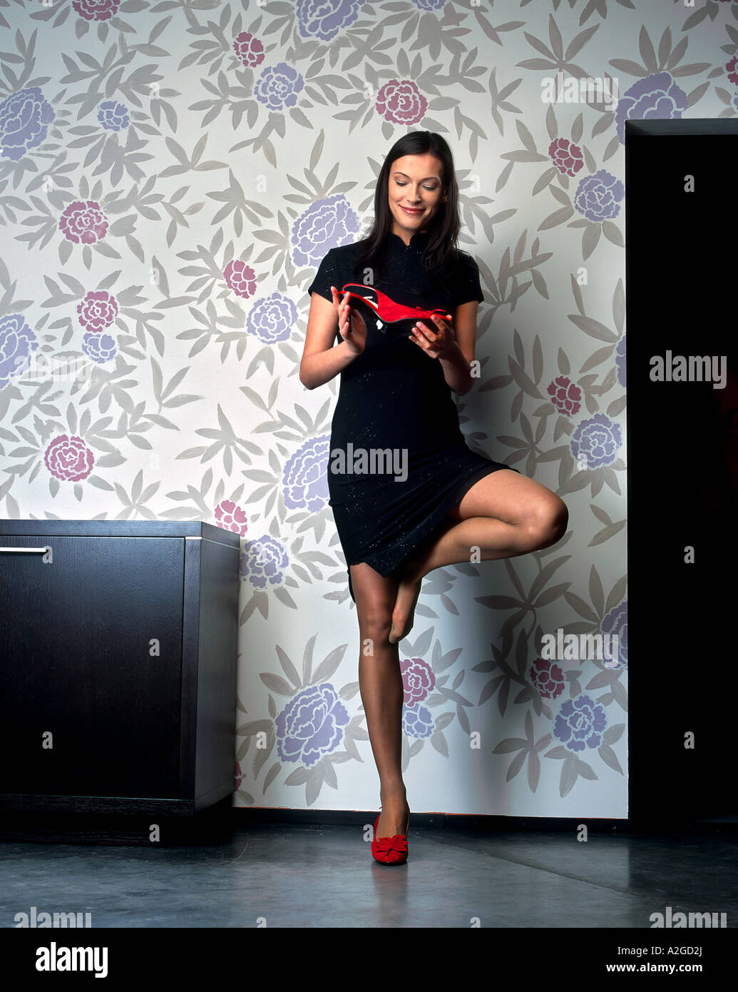 1216452 indoor flat room young woman 25 30 brunette long hair black dress put on red shoe shoes hold look stand - Stock Image