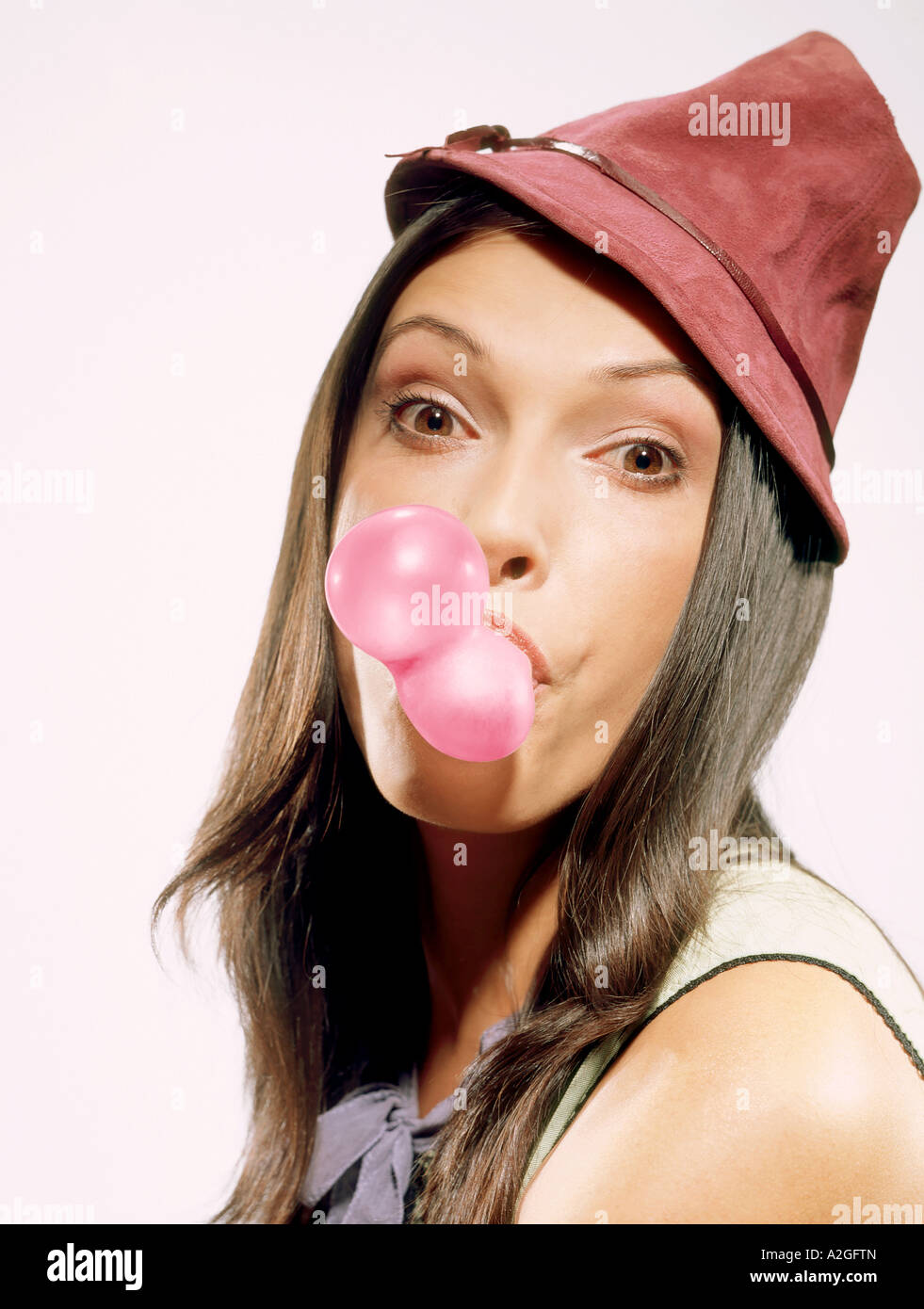 1216613 indoor studio young woman 25 30 brunette long hair hat pink chewing gum bubble bubbles fun play close up - Stock Image