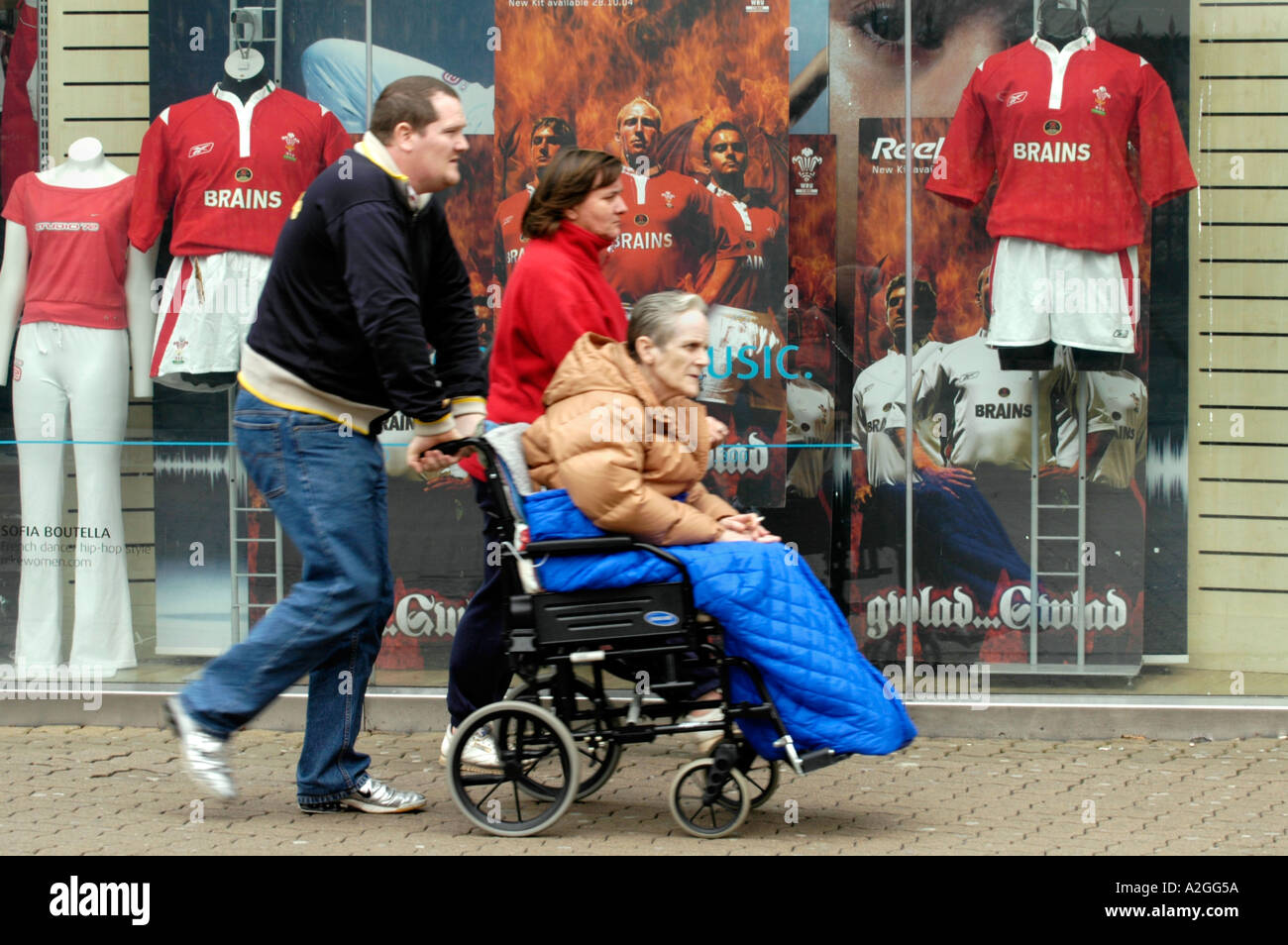 Elderly lady in wheelchair being pushed past sports shop window display in Cardiff city centre Wales UK - Stock Image