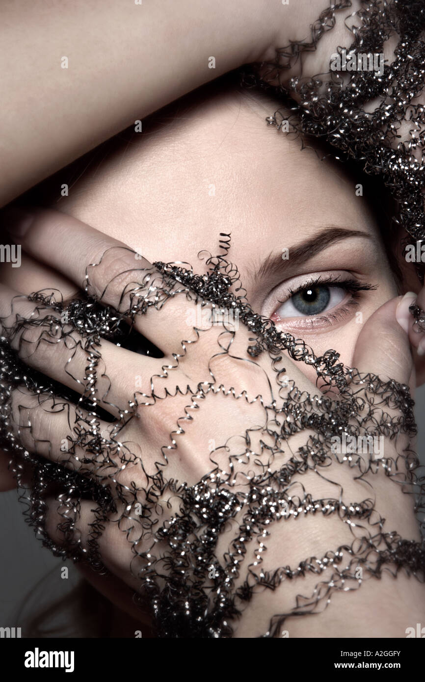 1217497 indoor studio young woman 25 30 brunette hand hands wire wires shavings shaving glove gloves symbol touch - Stock Image