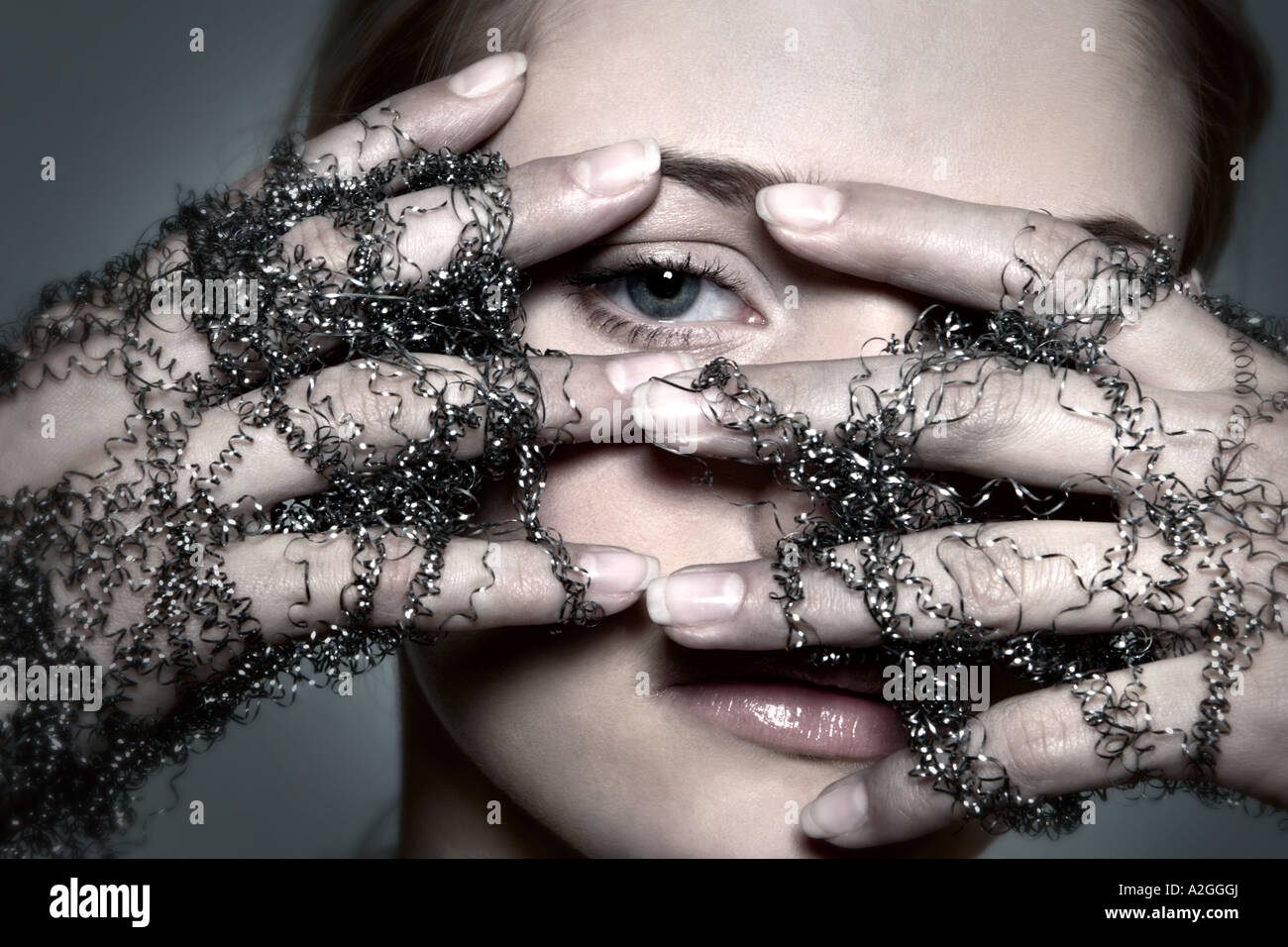 1217498 indoor studio young woman 25 30 brunette hand hands wire wires shavings shaving glove gloves symbol touch - Stock Image