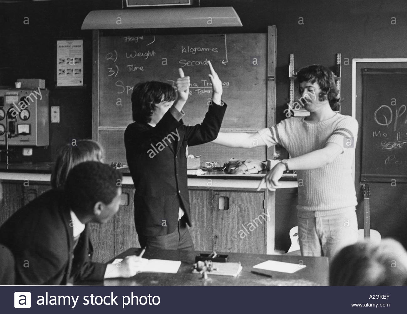 secondary school teacher trying to control a disruptive student in classroom Stock Photo
