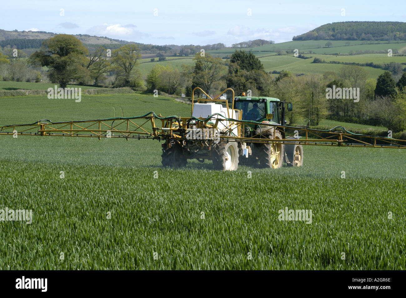 A John Deere tractor and trailed Knight sprayer spraying a young wheat crop in spring - Stock Image