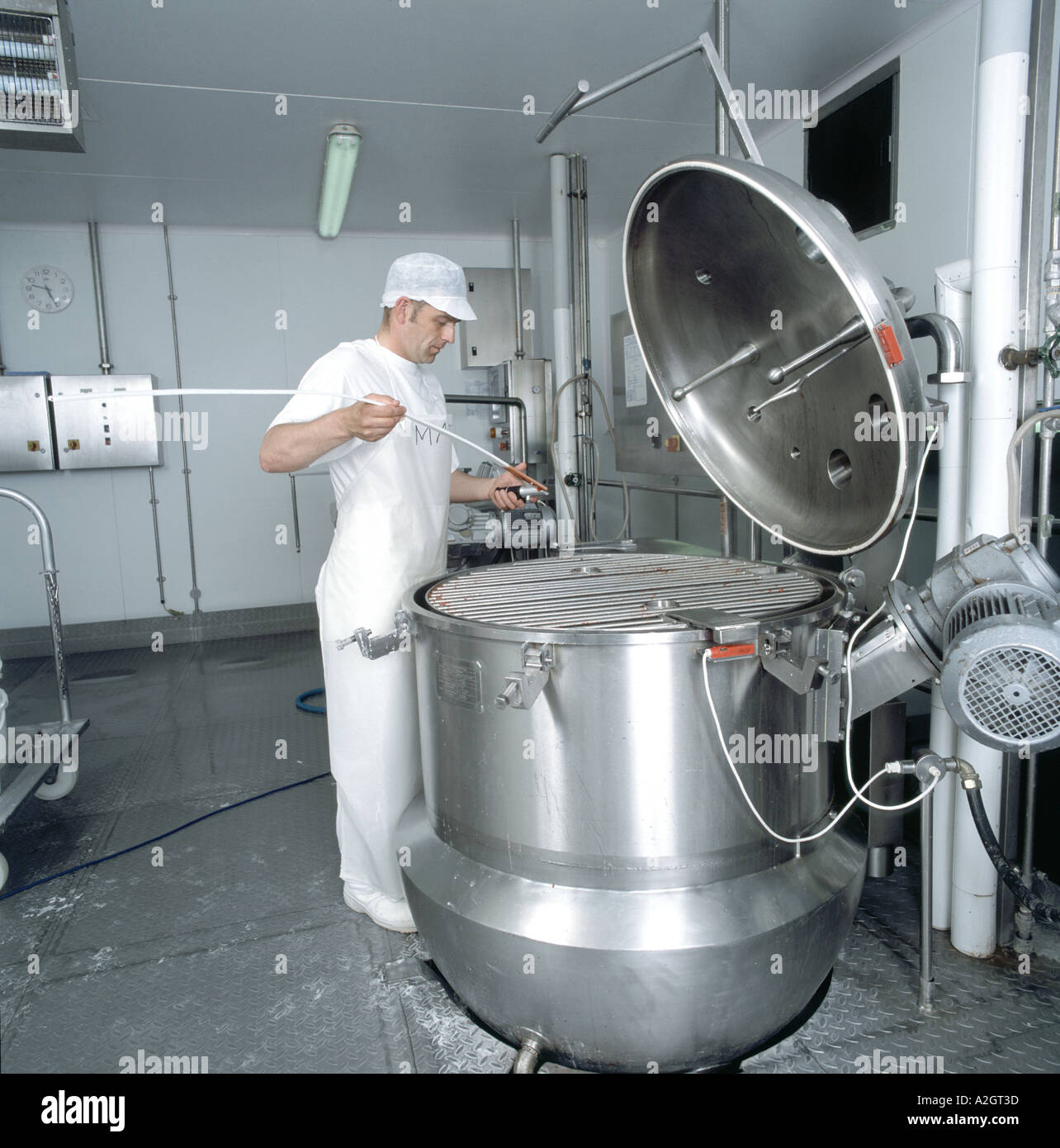 Man testing fruit being cooked in stainless steel boiler for Stock ...
