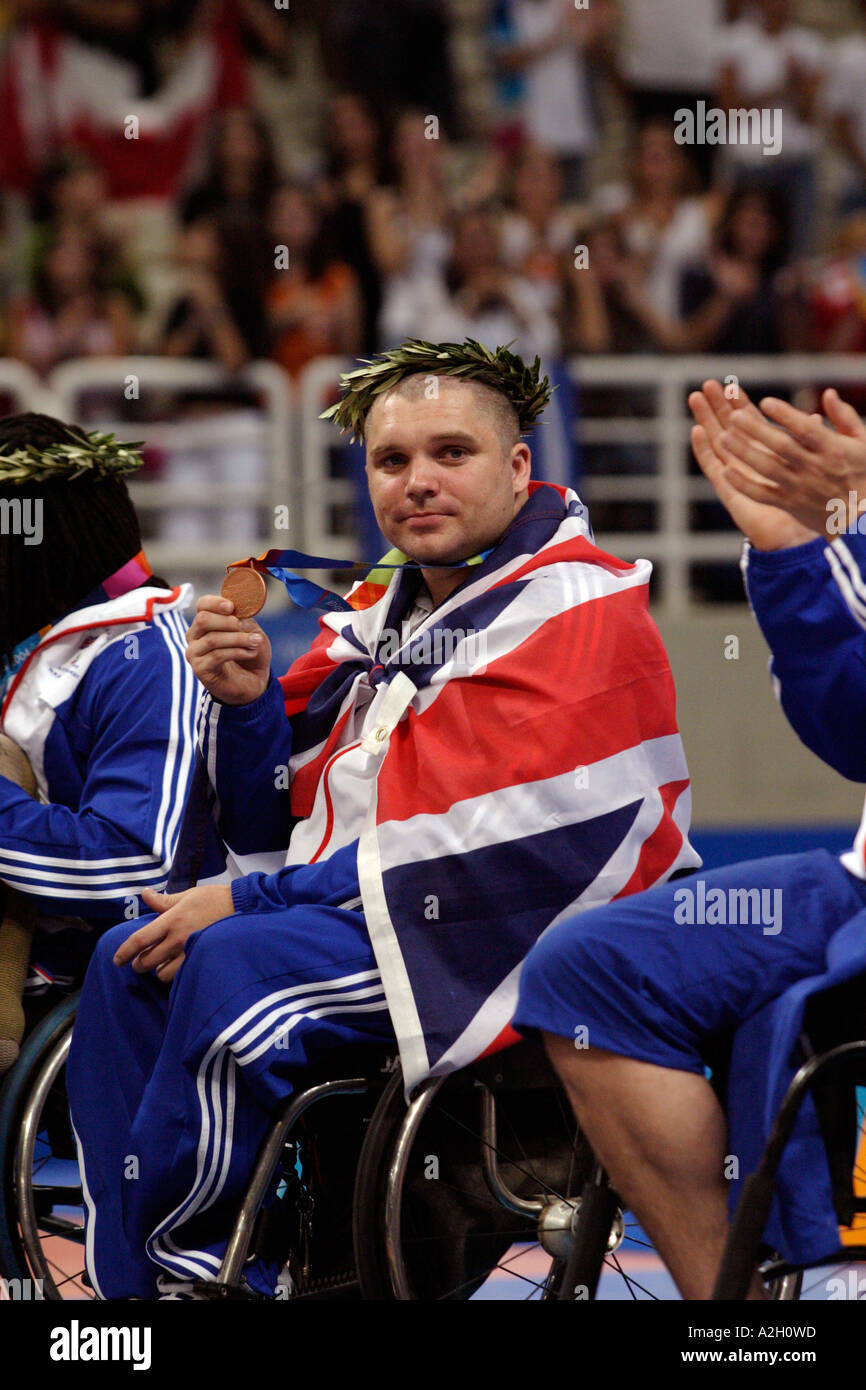 Draped in the Union Jack Jon Pollock of GBR shows his bronze medal for the mens open basketball Athens 2004 Paralympic Games - Stock Image