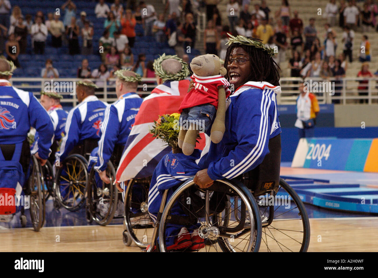 Ade Adepitan of GBR after receiving his bronze medal for the mens open basketball plays to the crowd with his monkey mascot - Stock Image