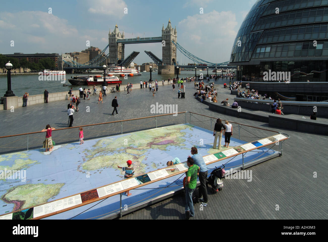 Riverside walkways at Greater London Authority City Hall by River Thames & Tower Bridge with world map display for kids to study - Stock Image