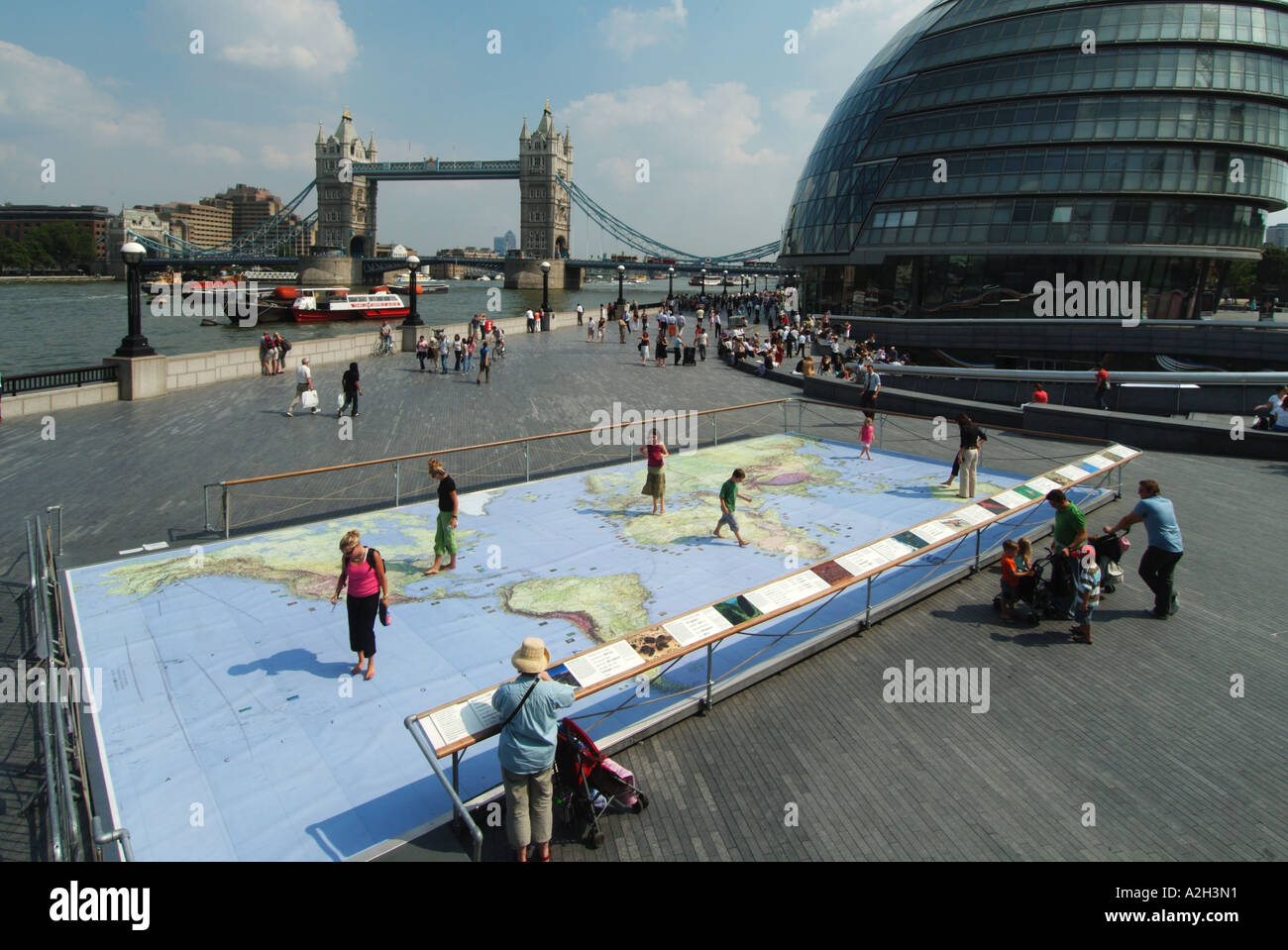 Riverside walkways at Greater London Authority City Hall by River Thames & Tower Bridge with world map display for Stock Photo