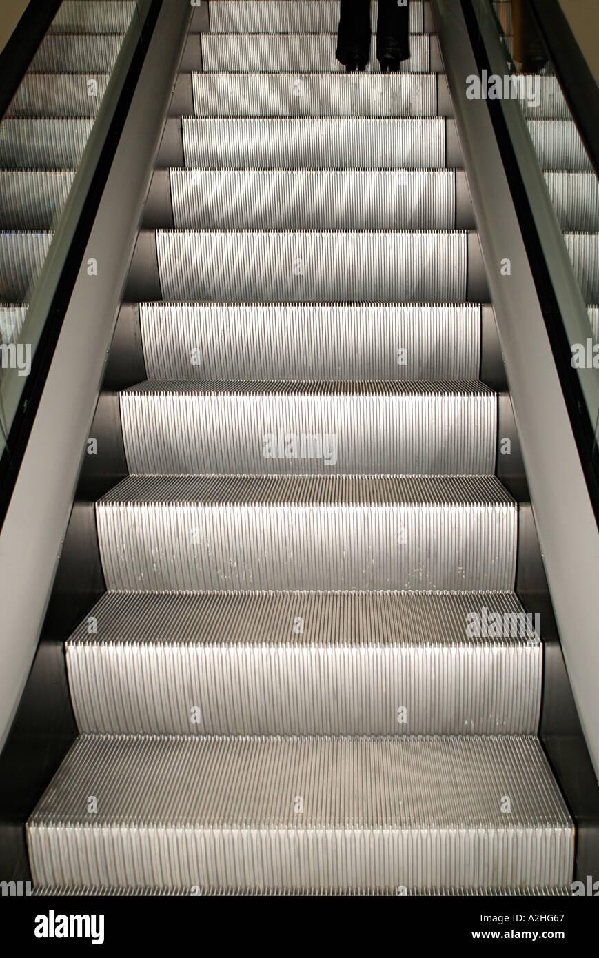 Girl Going Up an Escalator - Stock Image