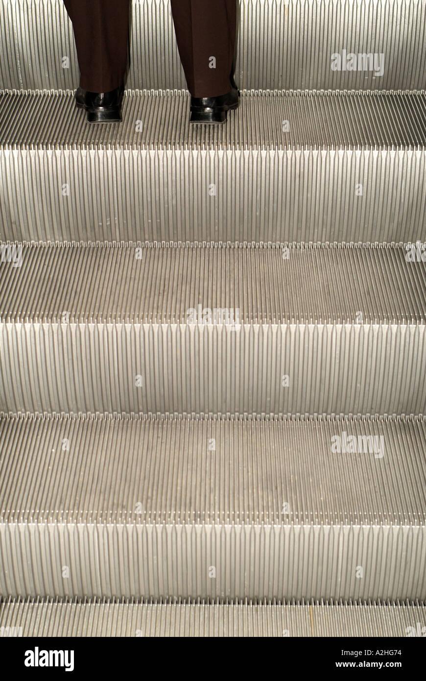 Businessman Going up an Escalator - Stock Image