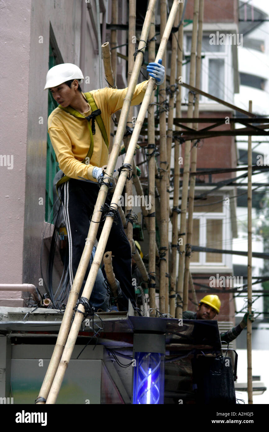 Construction men putting up bamboo scaffolding, Wan Chai, Hong Kong SAR - Stock Image