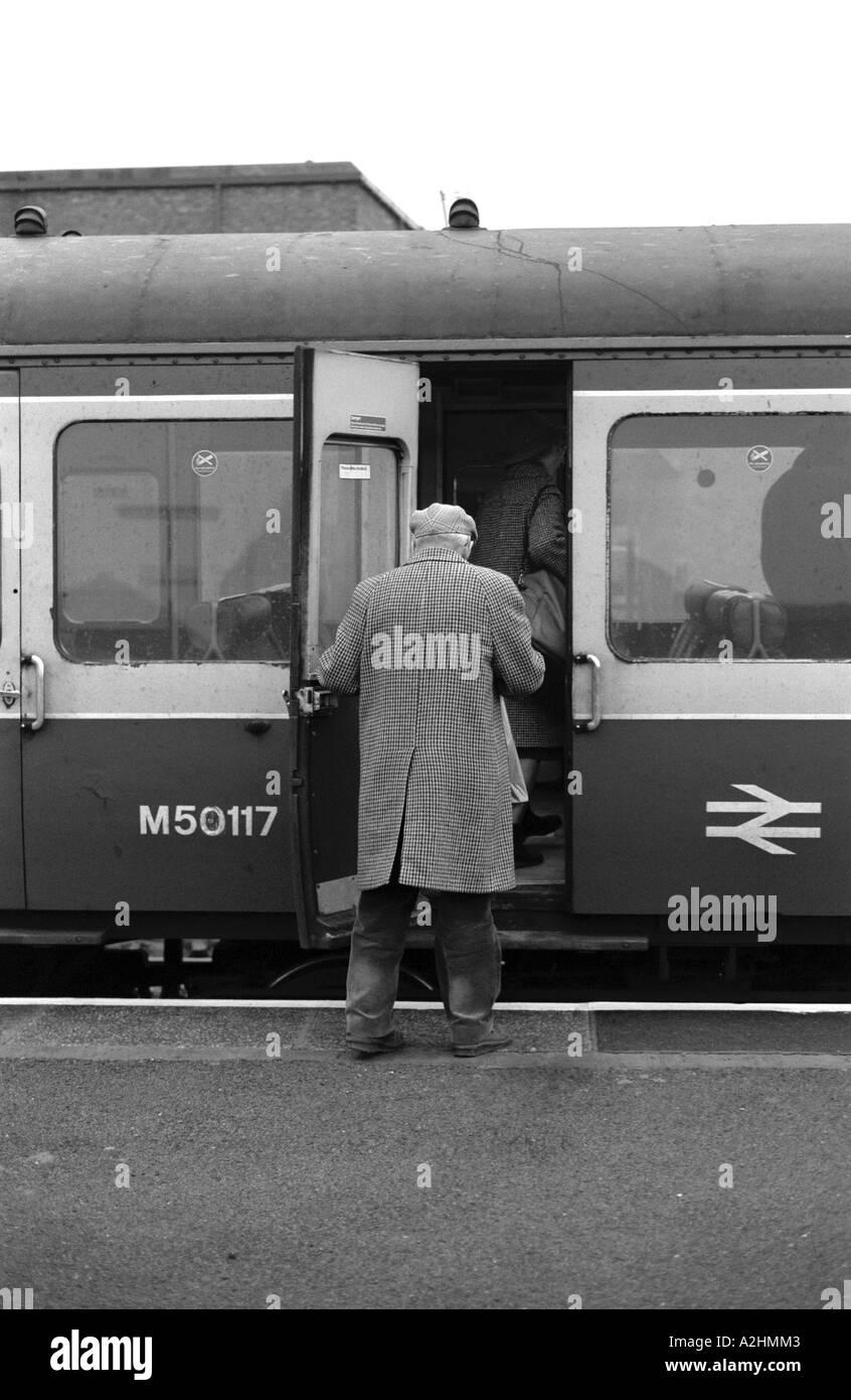 Elderly man boarding train at Stratford-upon-Avon railway station, Warwickshire, England, UK. January 1987 - Stock Image