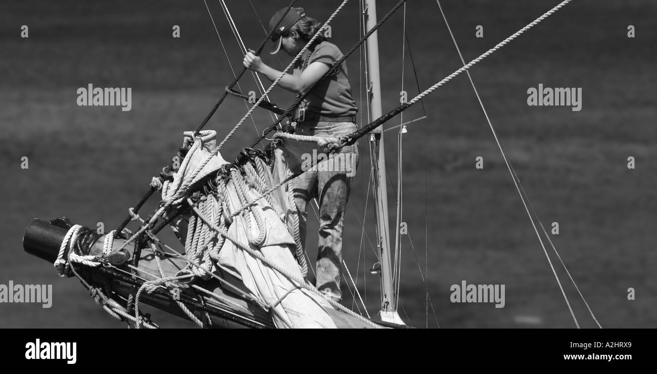 B/W of girl out to sea fixing the mast at the bow of a tall ship - Stock Image