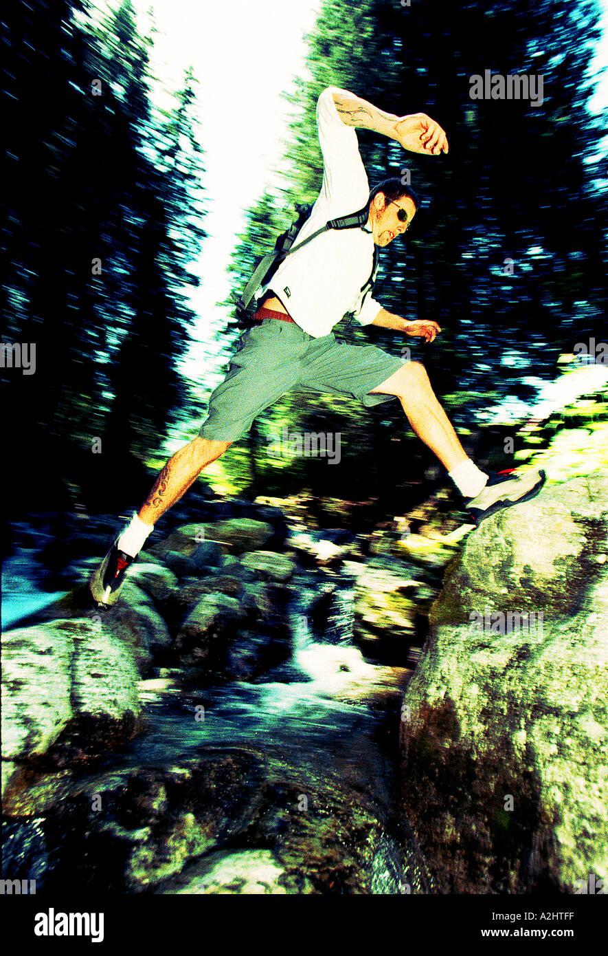 Man age 20-25 jumping a waterfall. - Stock Image