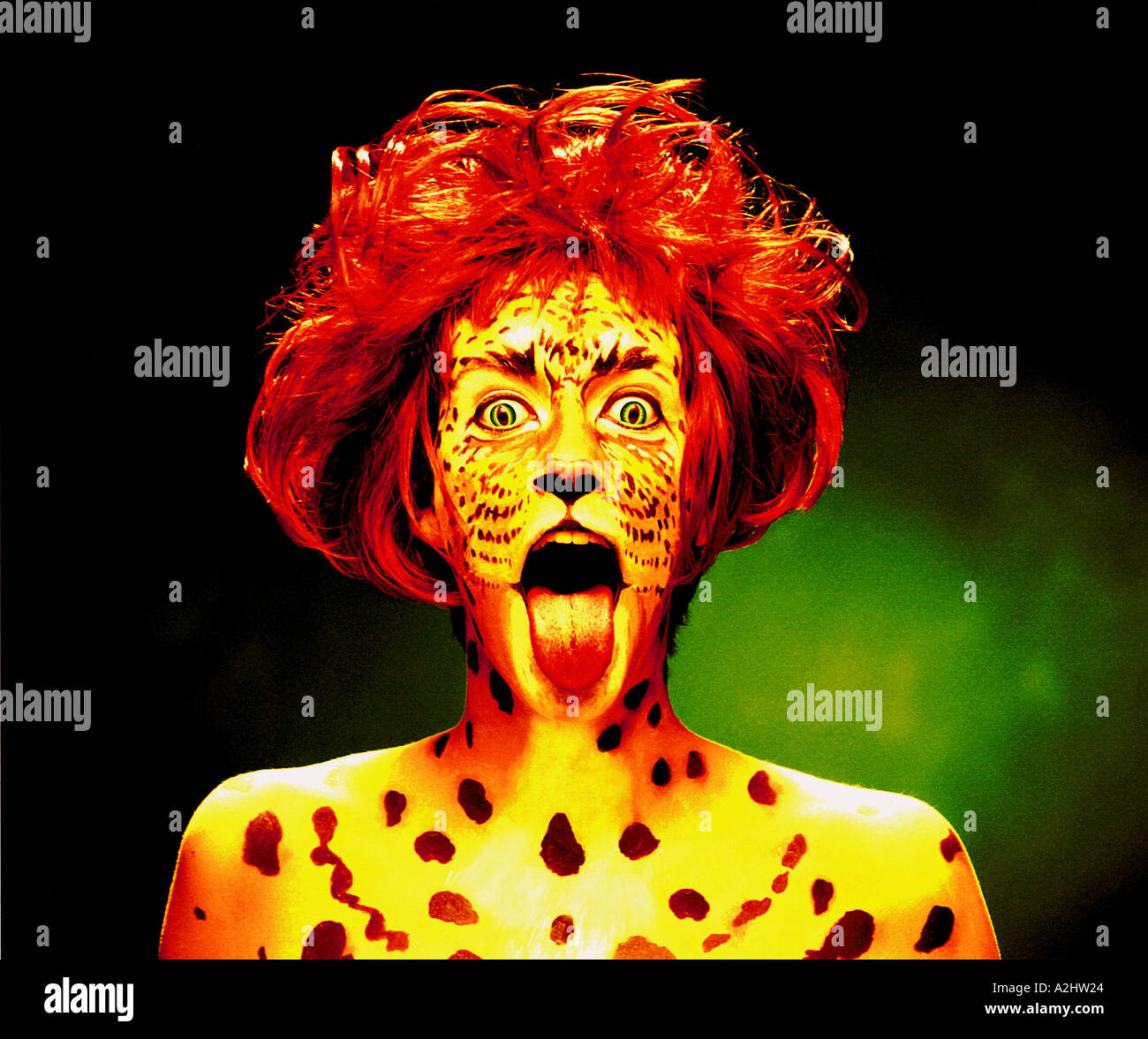 Woman age 20-25 with her face painted as a Tiger. She is wearing a red wig and has her tongue out. - Stock Image