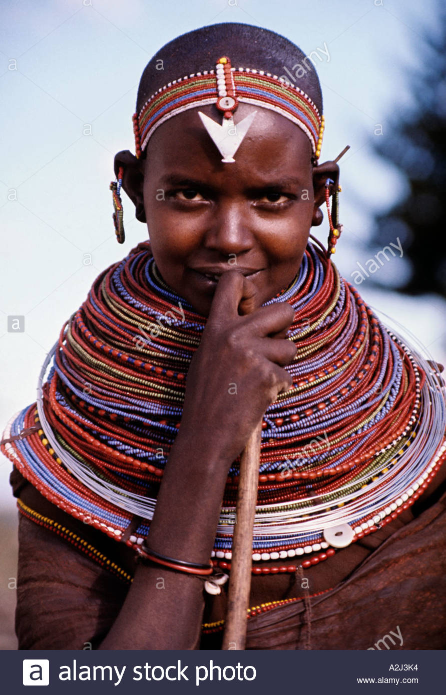 Samburu girl wears many beaded necklaces gifts from admirers The pendant on her forehead is a stylised aluminium bird - Stock Image