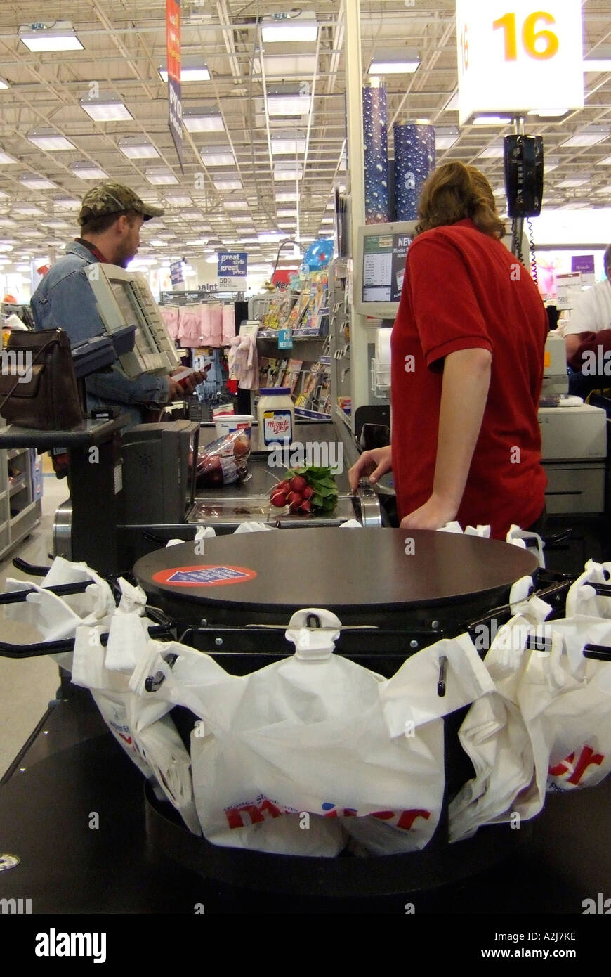 Woman stands at check out register to pay for groceries and other products in a Meijer superstore - Stock Image