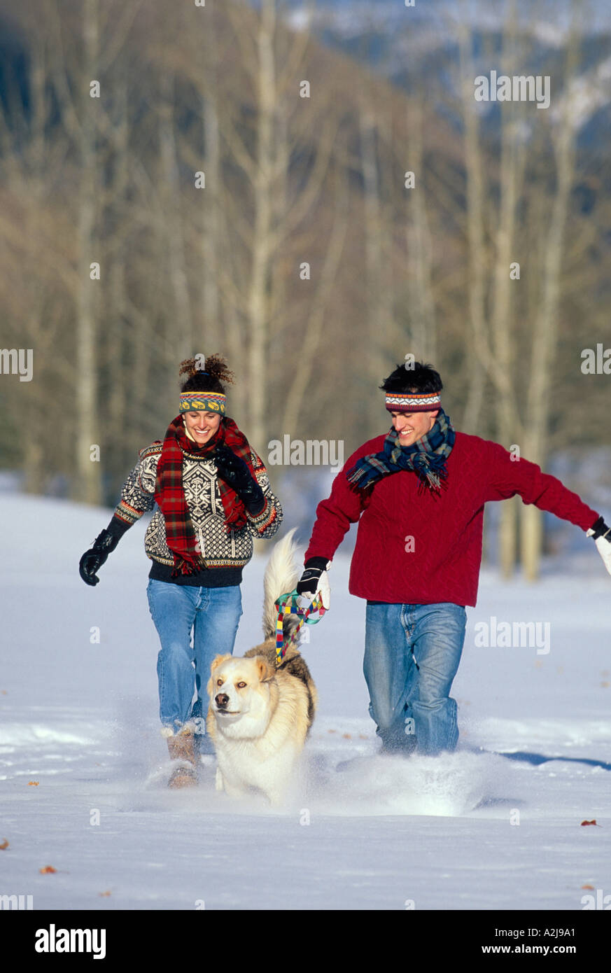 A man and a woman run through a snowy field with their dog - Stock Image