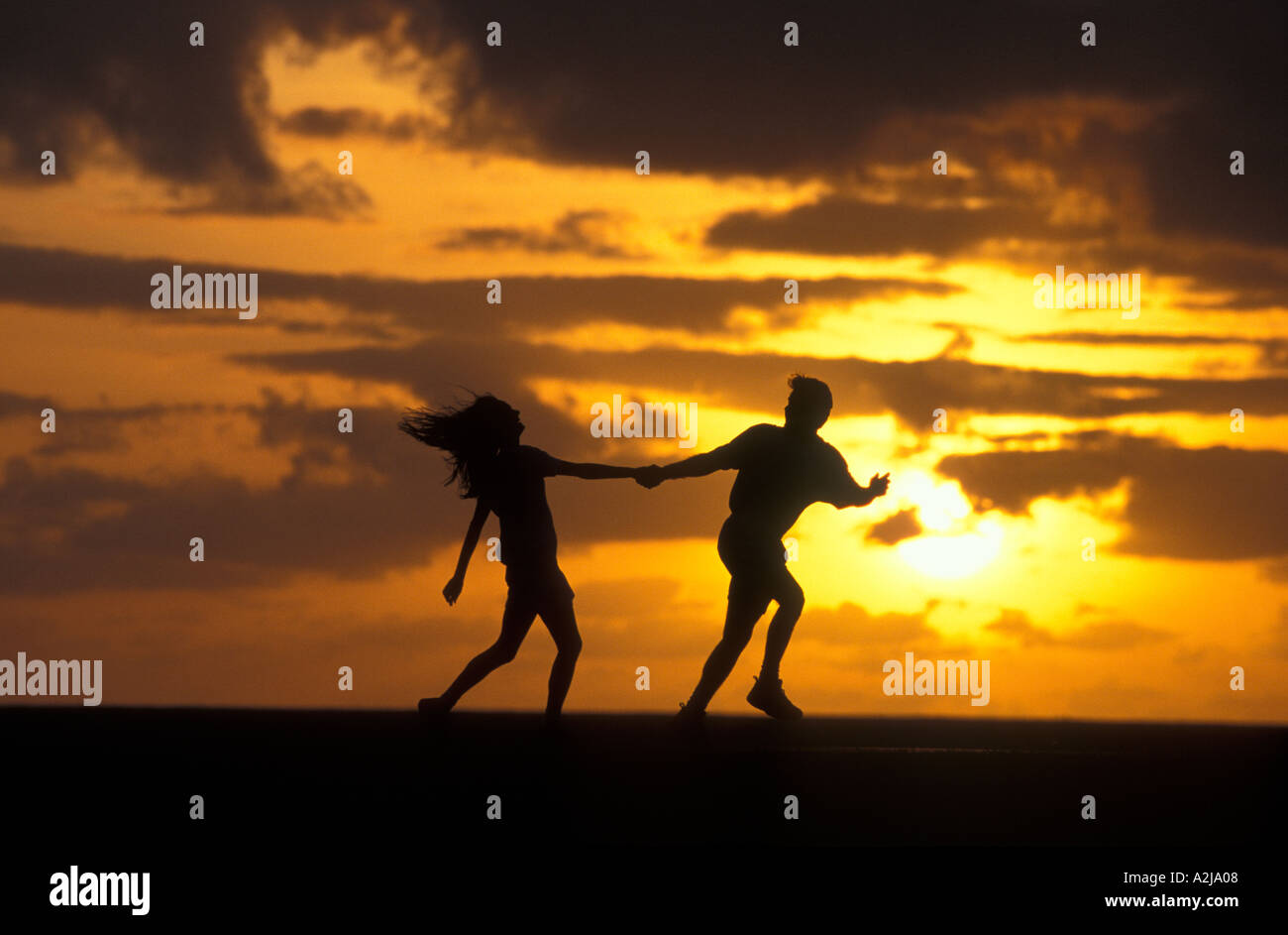 Man and woman running together playfully outdoors silhouetted against a golden sky Stock Photo