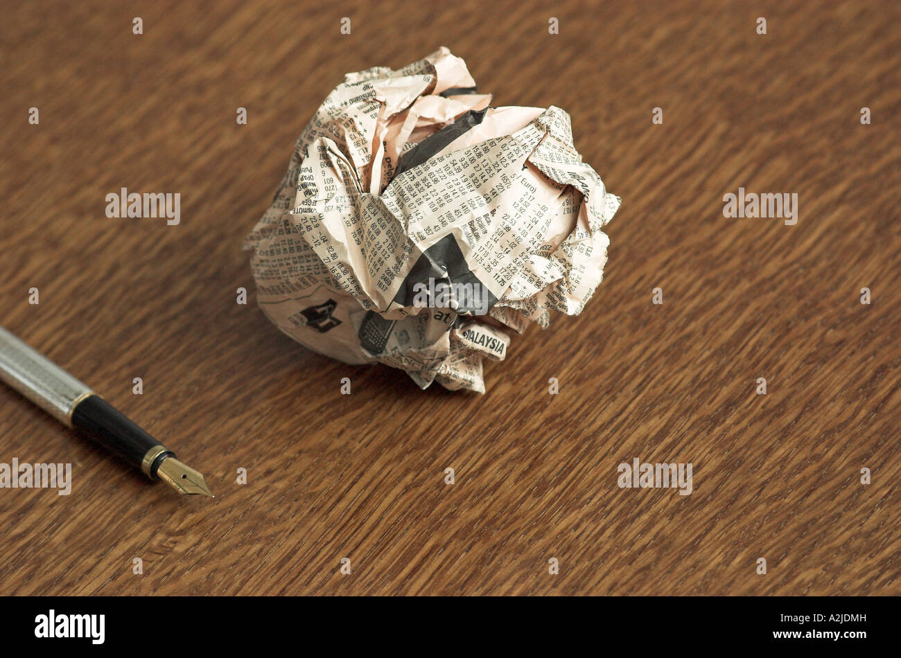 Scrunched ball of newspaper and fountain pen on table - Stock Image