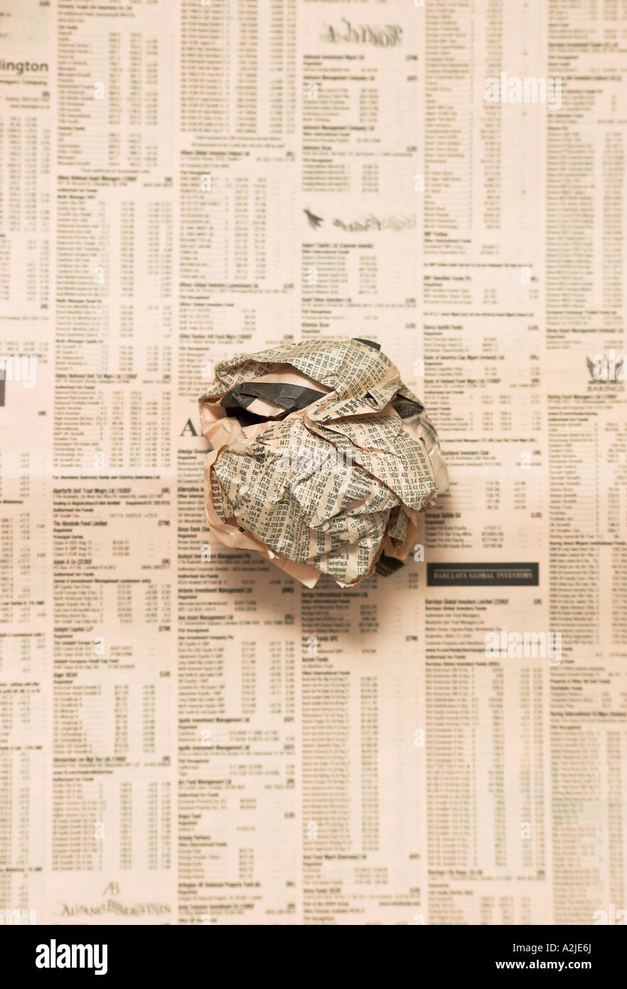 Scrunched ball of newspaper on flat page of newspaper - Stock Image