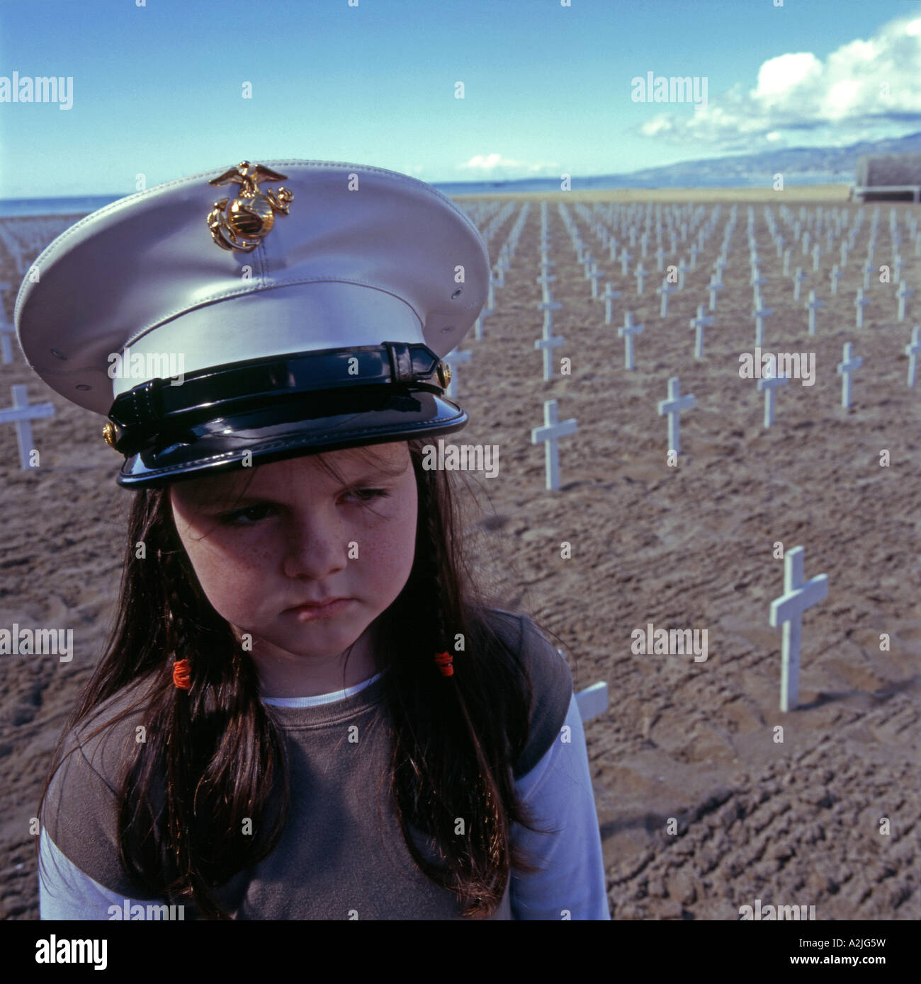 A child stands next to a sea of white crosses on Santa Monica beach, Los Angeles, California, USA. - Stock Image