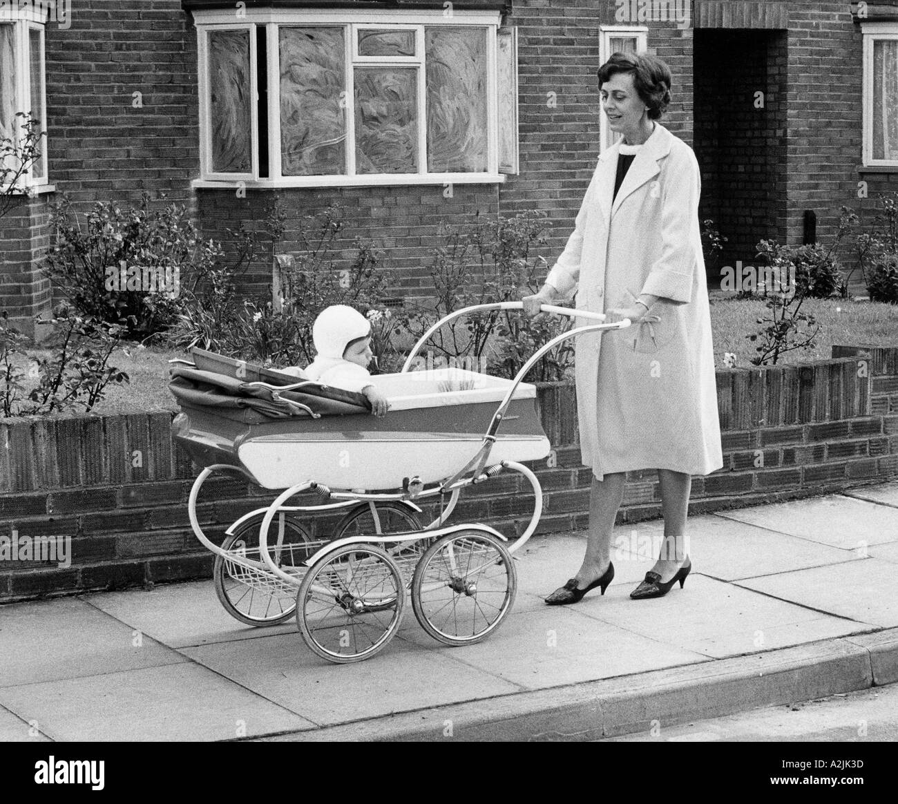 A 1950s mother wheels her baby in his new pram - Stock Image