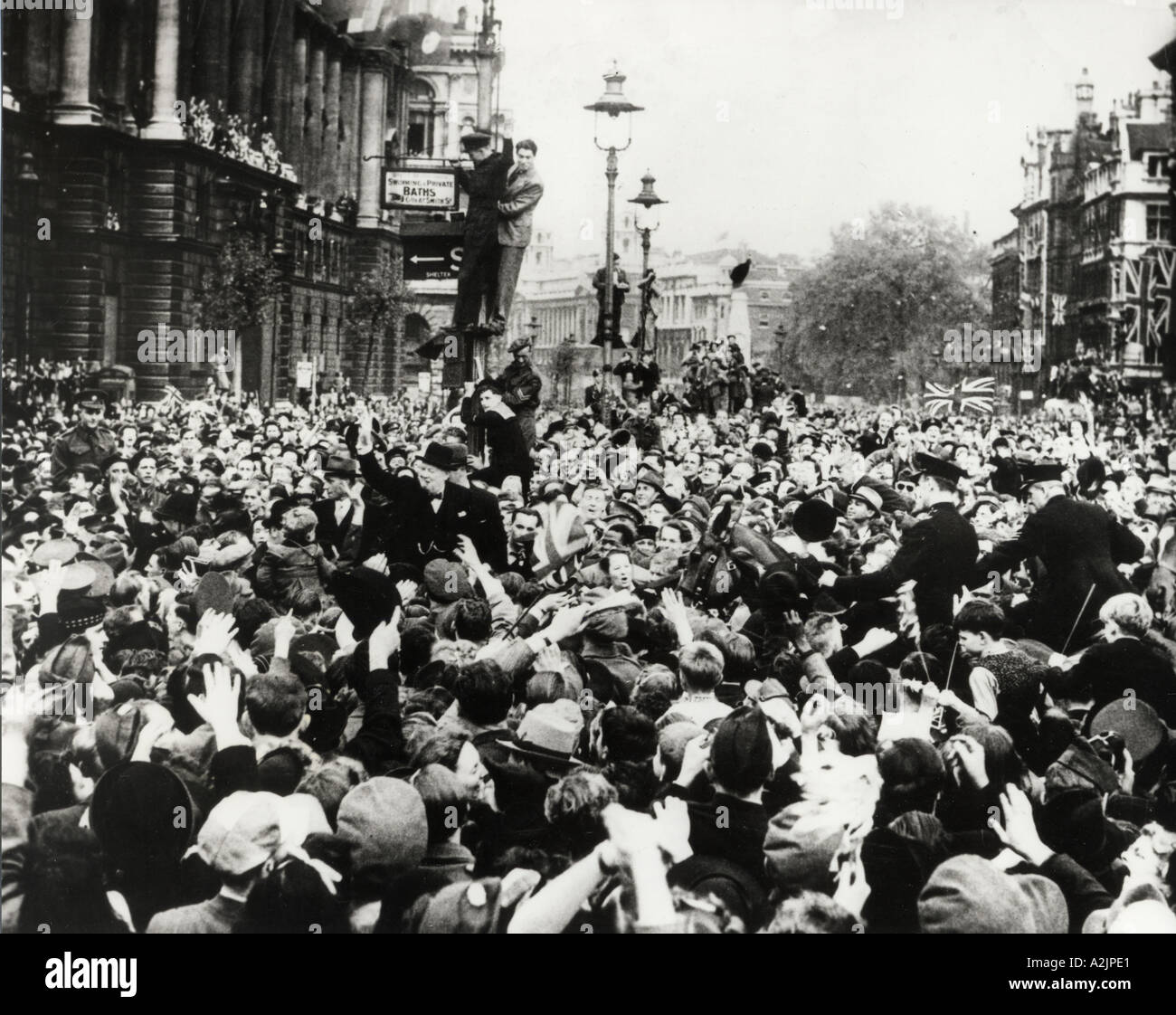WINSTON CHURCHILL is mobbed by jubilant crowds in Whitehall on VE Day 8 May 1945 - Stock Image