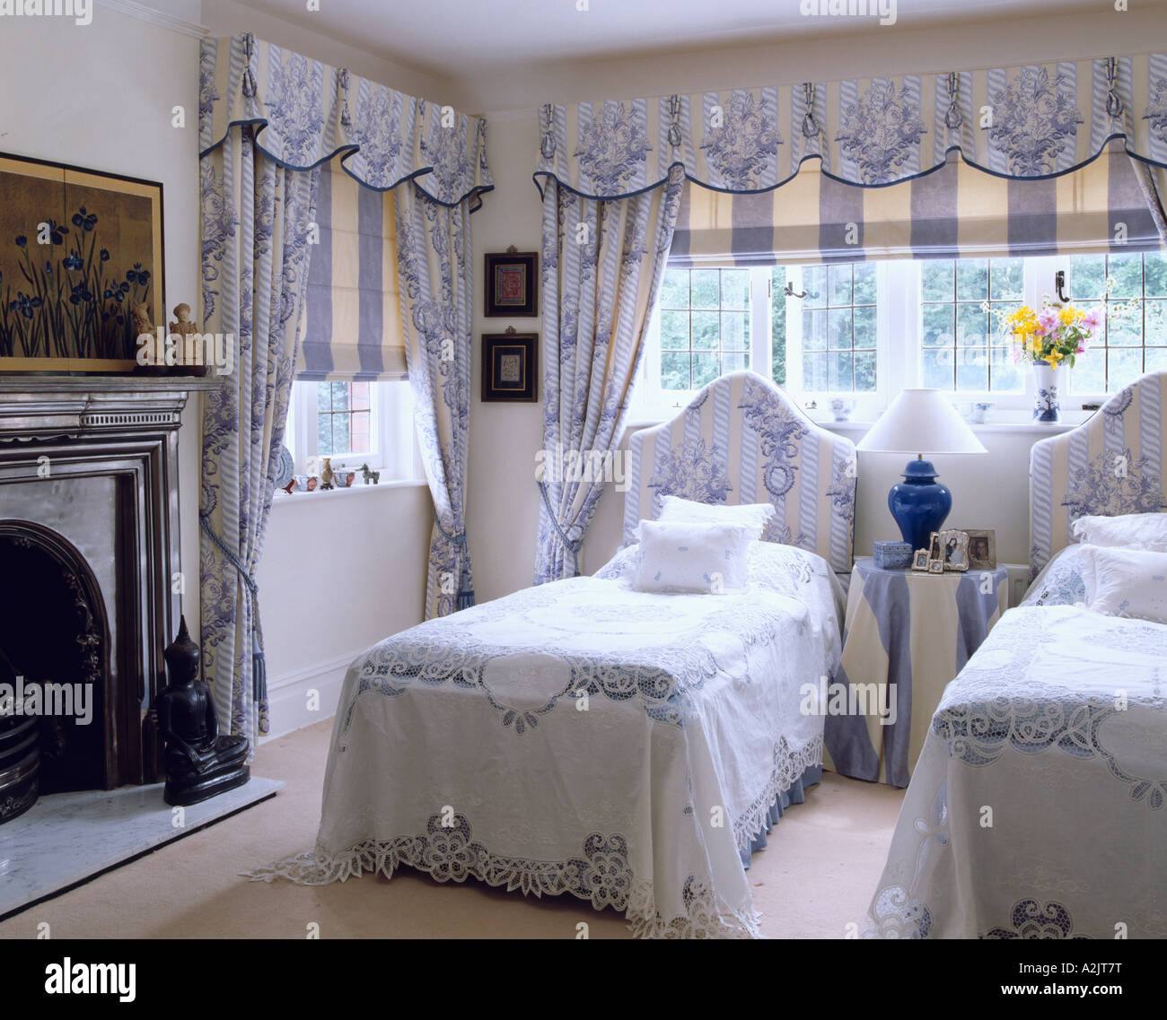 Bedroom with floral linen and curtains and striped blinds ...