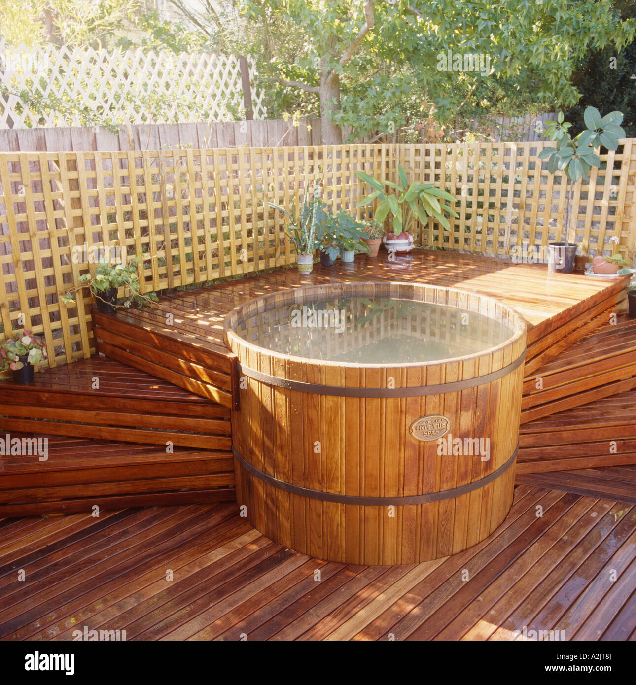 Circular hot tub on raised wooden decking with steps in townhouse ...
