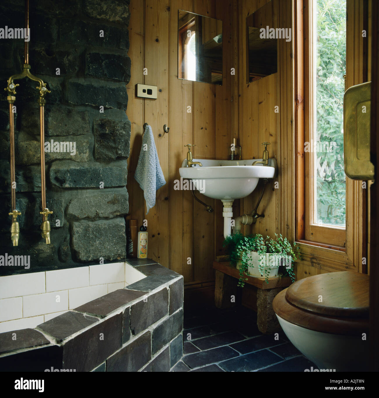 Corner basin in bathroom with wooden walls and black tiled bath ...