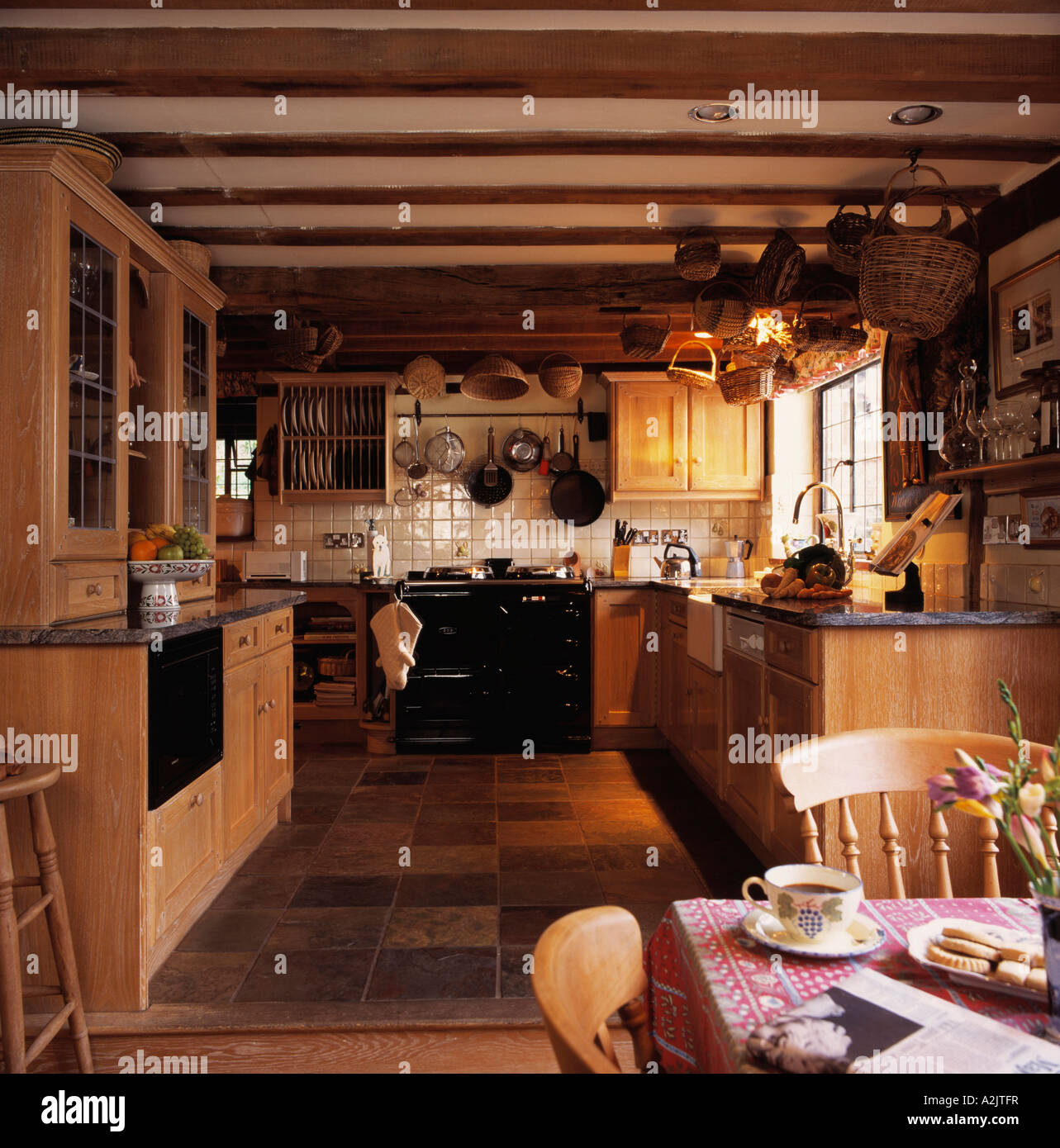 Country kitchen diningroom with aga and beamed ceiling - Stock Image