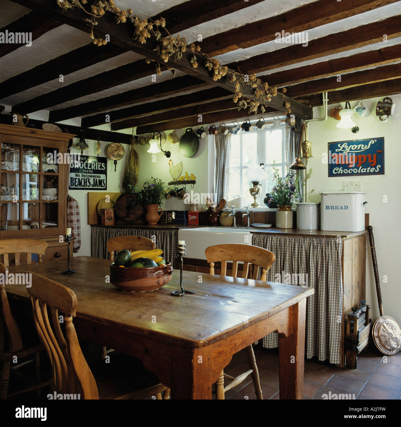 Cottage kitchen with dining table and dried hops on ceiling ...