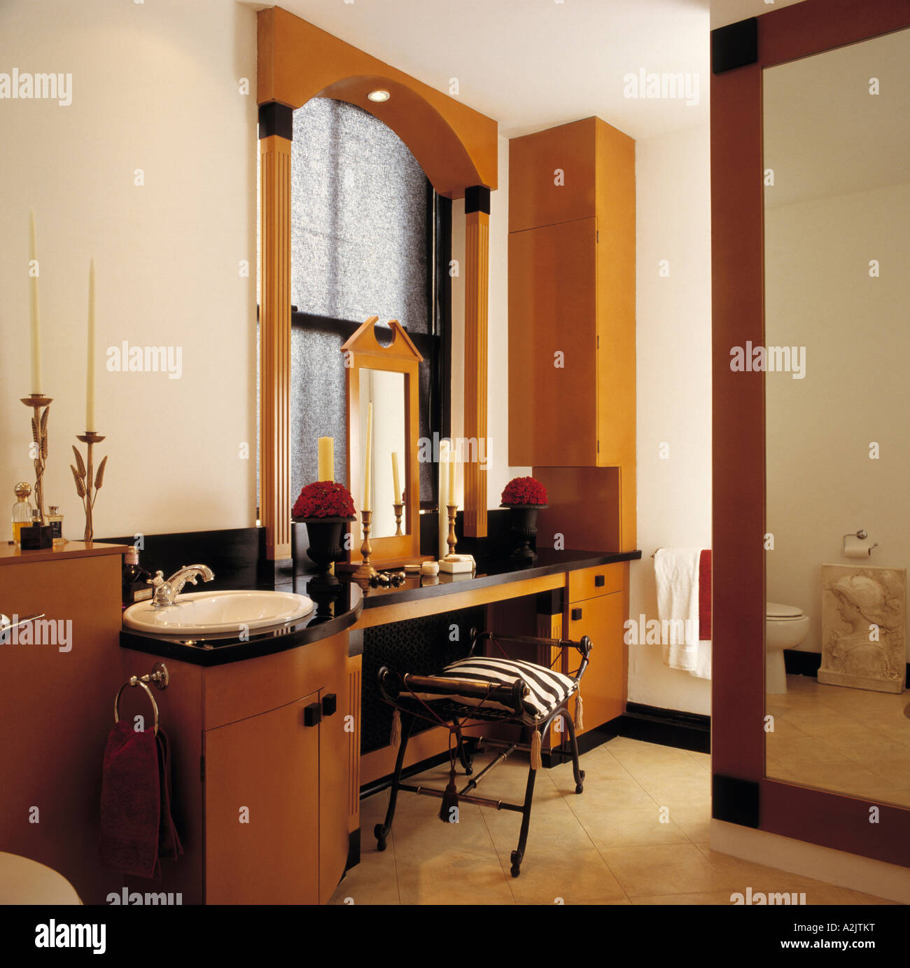Bathroom with pillared window frame and vanity unit with built in basin - Stock Image