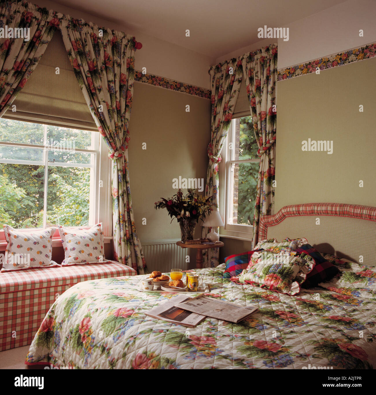 Floral quilt and curtains in green and pink bedroom Stock ...