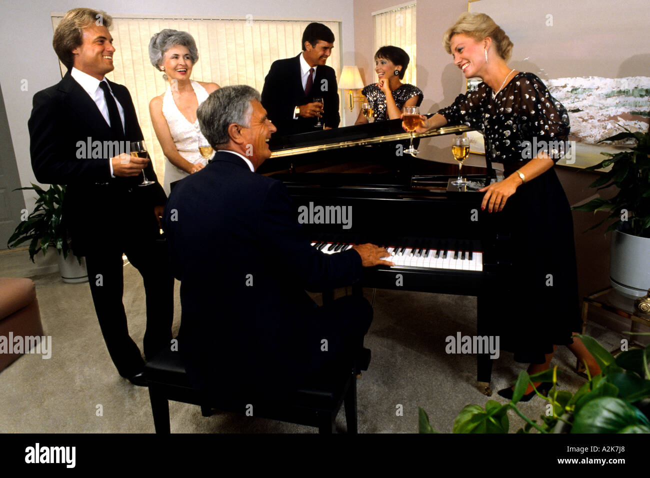 Elegantly dressed couples at dinner party playing the piano and having drinks in the good life - Stock Image