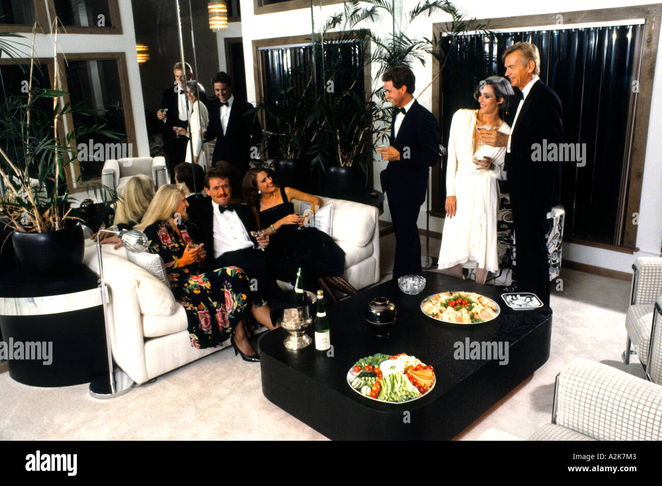 Elegantly dressed couples at dinner party social enjoying talking and having drinks in the good life - Stock Image