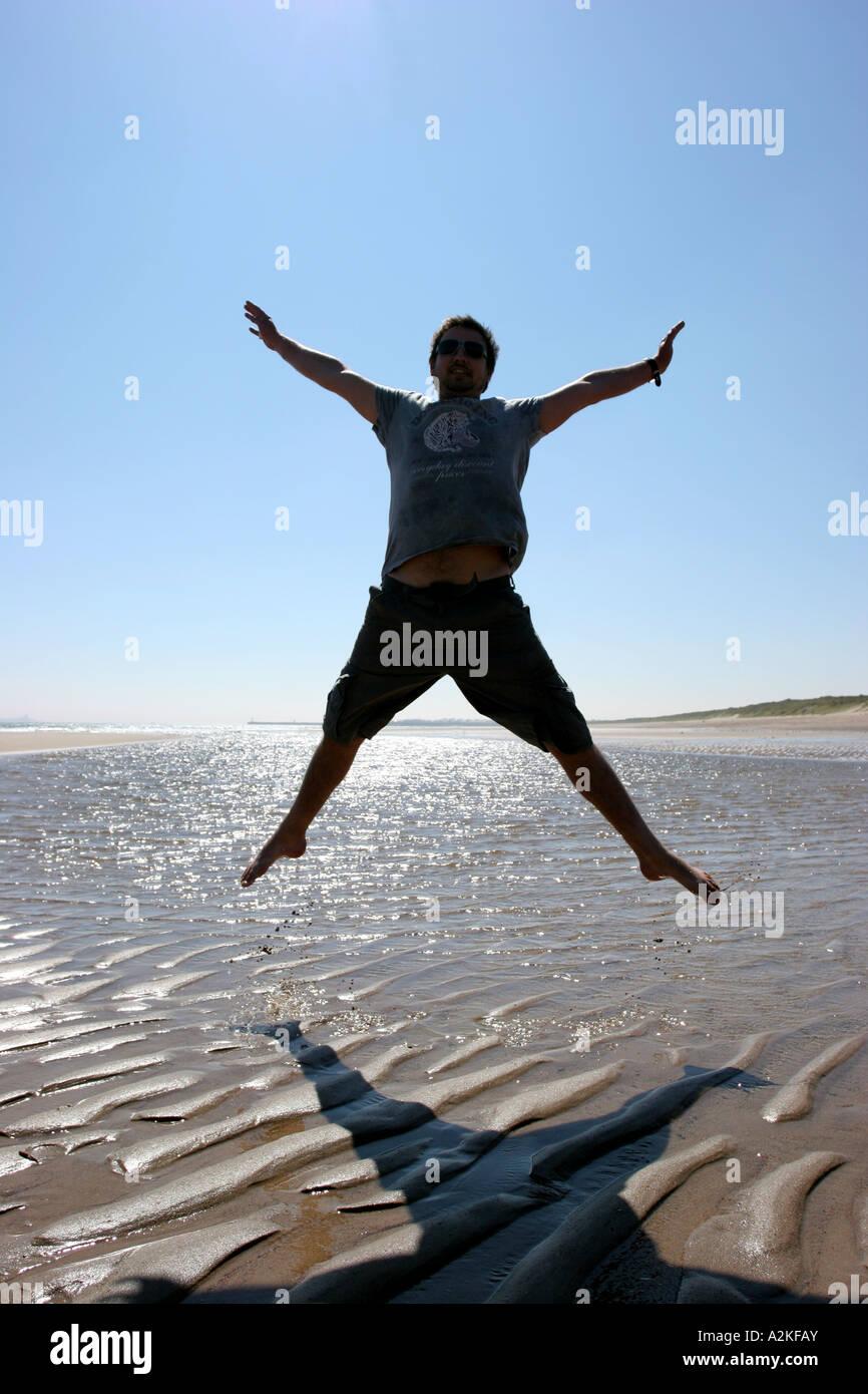 Man star jumping - Stock Image