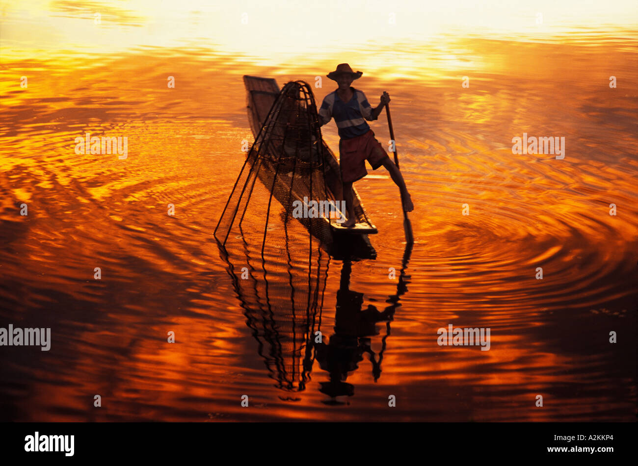 Intha fisherman rowing boat with legs and fishing at sunset Inle Lake Myanmar - Stock Image